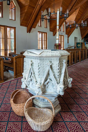 Los Olivos, California, USA - September 3, 2020: Closeup of white stone decorated baptismal font at St. Marks in the Valley Church with brown wooden ceiling and benches behind.