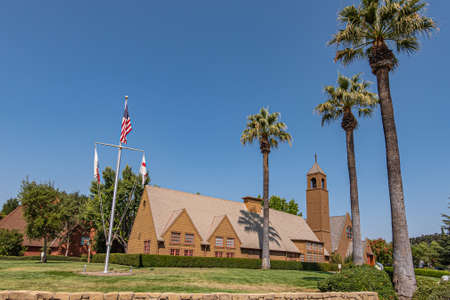 Los Olivos, California, USA - September 3, 2020: Wide view on brown wood St. Marks in the Valley Church with bell tower set in green park under blue sky, including side buildings. Flag post up front. Editorial