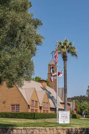 Los Olivos, California, USA - September 3, 2020: Portrait of brown wood St. Marks in the Valley Church with bell tower set in green park under blue sky, including side buildings. Flag post and info poster.