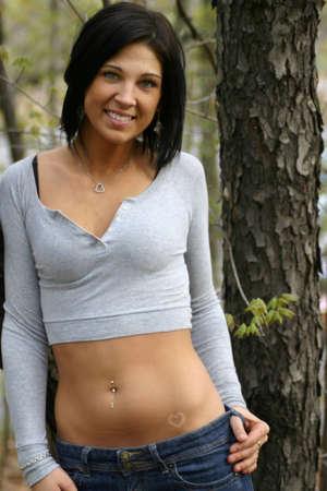 belly button: Nariz hermosa morena con piercing y ombligo piercing en el bosque