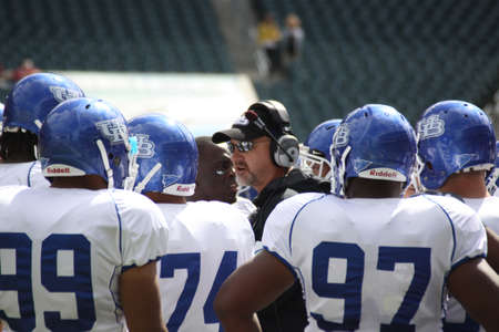 PHILADELPHIA, PA. - SEPTEMBER 26 : University of Buffalo defensive line coach, Brian Mohnsen, talks to his players on the sidelines on September 26, 2009 in Philadelphia, PA.