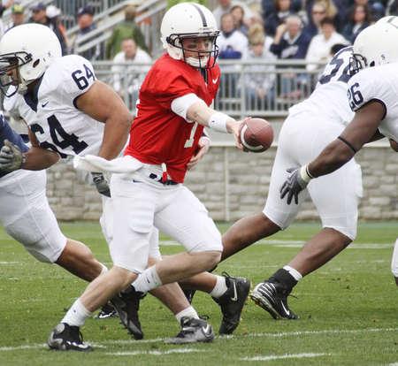 quarterback: UNIVERSITY PARK, PA - APRIL 24: Penn State quarterback Matt McGloin #11 hands the football off at Beaver Stadium April 24, 2010 in University Park, PA