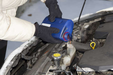 antifreeze: Adding radiator fluid in car radiator system, on cold winter day