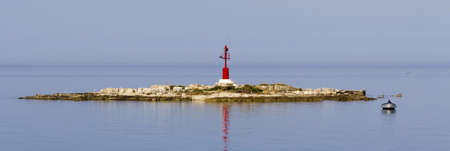 Panorama of small island with red beacon and fisherman in boat photo