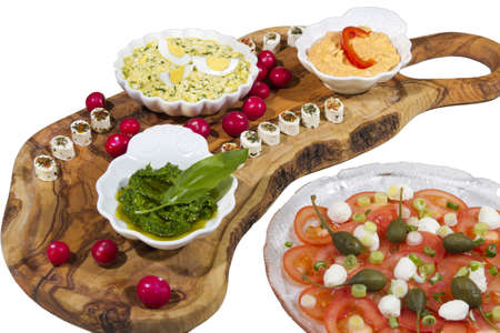 Delicius organic food on olive tree plate and tomatoes with  capres and mozzarella, isolated on white photo