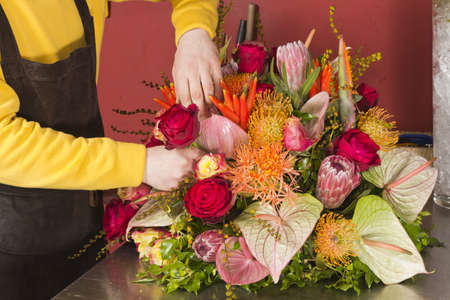 Florist finishing beautiful and rich flower arrangement
