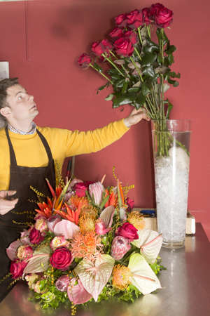 Florist picking red roses for rich flower arrangement photo