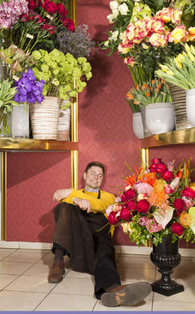 Happy male florist resting after hard work in his flower shop photo