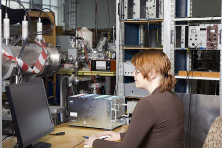 Young scientist inspects and controls the work of ION accelerator photo