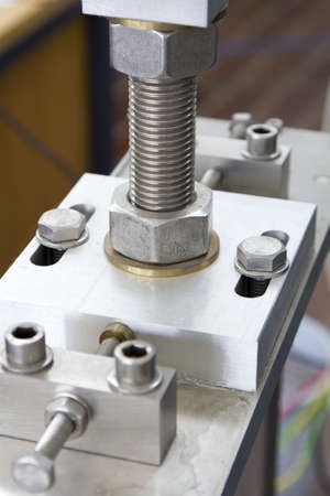 CNC machined part with visible screws and nuts - close up photo