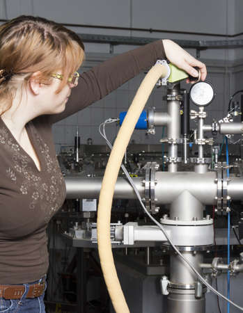 Young scientist inspects and controls the electronic parts of ION accelerator photo