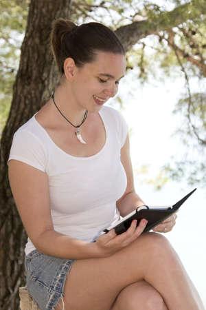 e reading: Cute girl reading new tablet e-reader in garden near sea coast