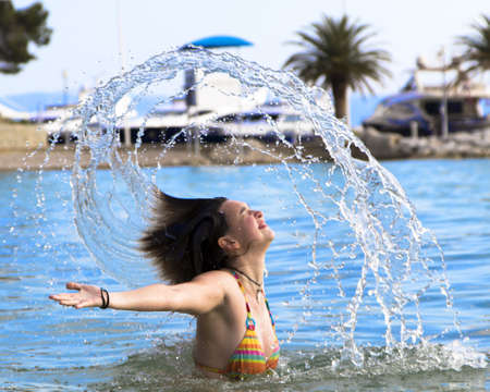 Cute young girl splashing out of the water on the beach photo