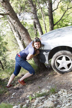 Girl pushes car after accident on wood road Stock Photo