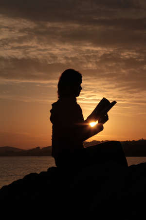 Reading book on the rock near sea at sunset-silhouette