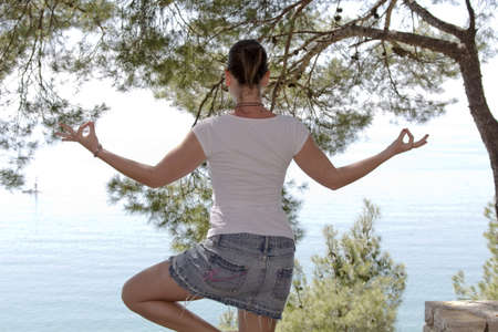 Girl performing yoga in the pine wood over  the sea photo
