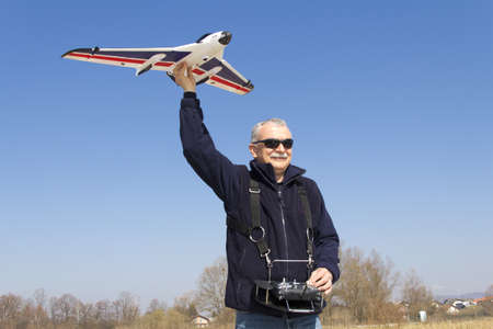 controlled: Happy man launching a remote controlled airplane into the air