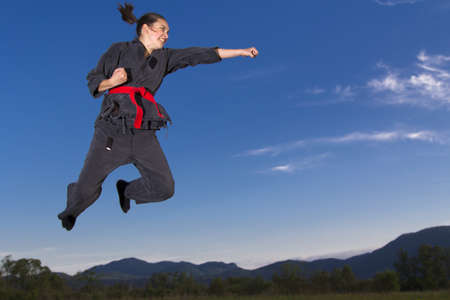 Woman ninja in an aggressive posture flying in the air photo