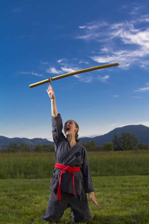 ninjutsu: Woman ninja outdoor throwing sword in the air