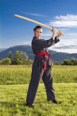 Woman ninja in an aggressive posture with a katana sword photo
