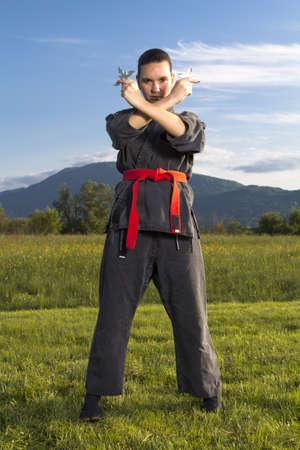 shuriken: La mujer ninja en una postura agresiva con los shuriken Foto de archivo