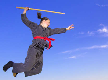 Woman ninja in an aggressive posture flying with katana photo