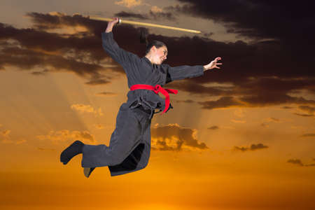 ninjutsu: Woman ninja in an aggressive posture flying with katana on sunset