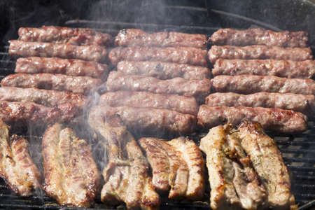 BBQ Ribs and cevapcici during grilling Close Up