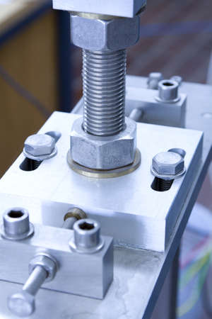 Screw and nut on CNC machined part close up photo