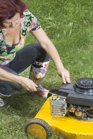 Woman repairs yellow lawn mower in the garden photo