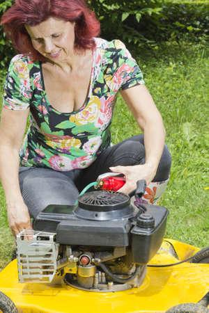 잔디를 깎고 동안 잔디 이동기를 주유 여성 Smilling 소수