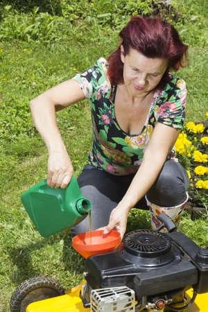 잔디 깎는 기계에 기름을 첨가 한 중년 여성 스톡 콘텐츠