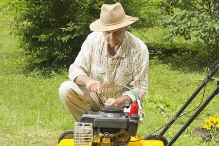 정원에서 잔디 깎는 기계를 수리 중년 남자 스톡 콘텐츠