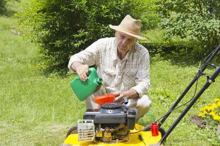 중간 나이 남자 정원에서 잔디 발동기에 기름을 추가 스톡 콘텐츠