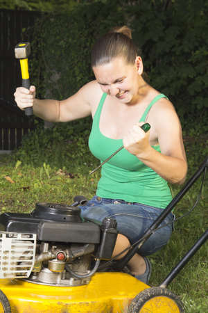 Angry girl breaking in pieces old lawn mover outdoors photo