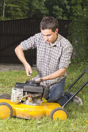 Man oiling and repairing yellow lawn mower