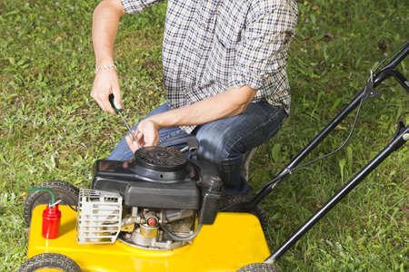 노란 잔디 깎는 기계를 수리하는 사람 (남자) - 가까이 스톡 콘텐츠