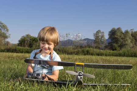 Cute young boy and his RC plane, sitting on grass photo