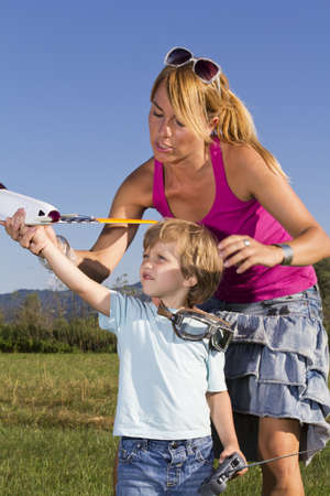 Cute mother demonstrating her young son how to launch RC plane photo
