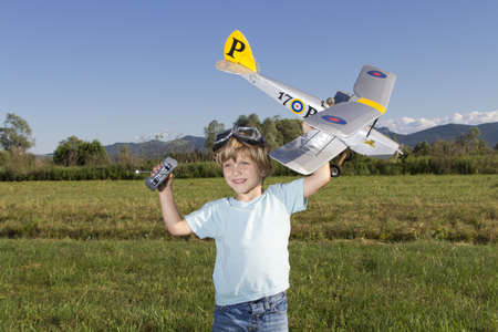 small plane: Smiling happy young boy preparing to launch RC plane