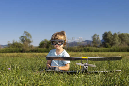 rc: 귀여운 어린 소년과 그의 RC 비행기, 잔디에 앉아