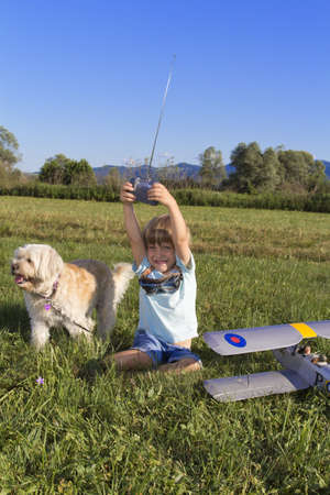 Happy Young boy and his new RC plane, sitting on grass with cute dog photo