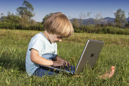 Young boy typing on notebook, sitting on the grass photo