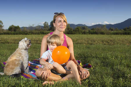 Cute young mother with 4 years old son enjoying sunny summer afternoon photo