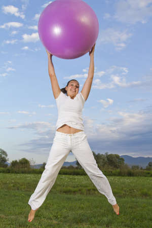 Cute young brunette girl performing yoga with a ball on green grass in park   photo