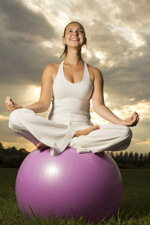 Cute young brunette girl performing yoga with a ball on green grass in park-dramatic sunset This photo  is part of a series of various yoga poses by this model  Stock Photo