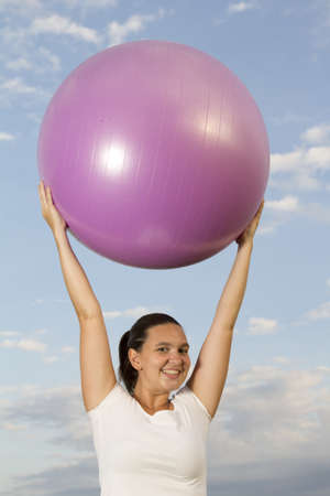 Cute smiling young brunet girl playing with big pink ball outside   photo