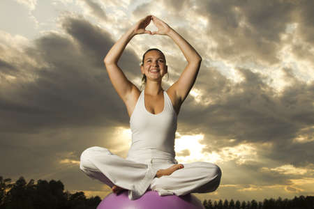 Young attractive brunette girl performing yoga outdoors-dramatic sunset