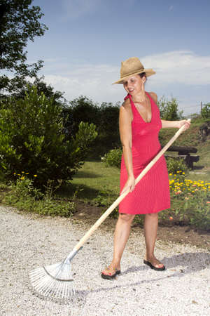 mid afternoon: Cute mid age woman with straw hat, raking the garden path on sunny afternoon Stock Photo