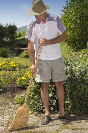 brooming: Middleaged man with straw hat brooming garden path on sunny summer afternoon